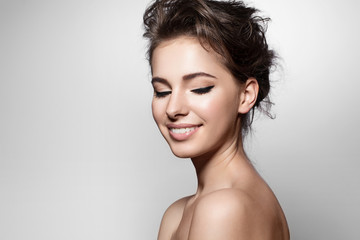 Beautiful woman with black arrows on eyes, clean skin and white teeth on grey background
