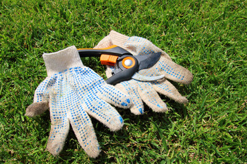 Modern secateurs and cotton knitted work gloves on the mown lawn in the summer garden