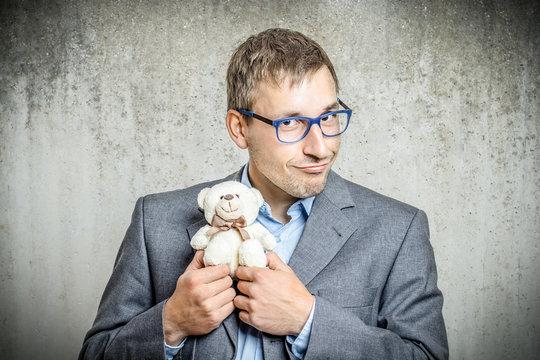 Mann im Sakko hält Teddybär