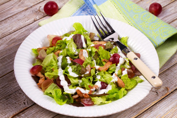 Chicken and red grape salad in white plate.