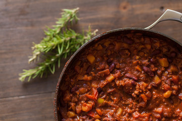 Organic Vegetarian Chili In Iron Pot Served With Rosemary On Dis
