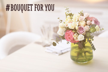 Beautiful bouquet of colourful roses in glass vase on the kitchen table