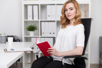 Woman reading book at work