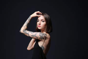 Beautiful young woman with tattoo posing on black background