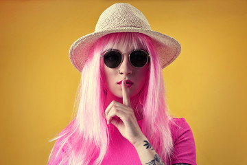 Beautiful young woman with tattoo wearing pink wig, hat and sunglasses on yellow background