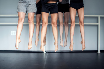Legs of a group of young dancers jumping tohether
