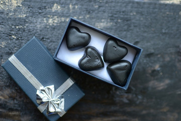black heart-shaped candy in a small black box next to the top cover with silver fat on a black background