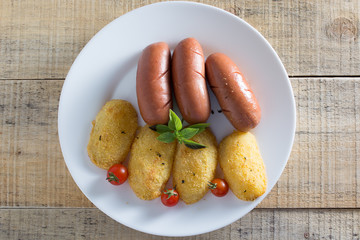 Fried sausages and breaded potatoes