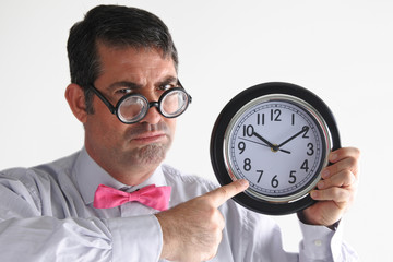 Frustrated man manager points to the time on a clock