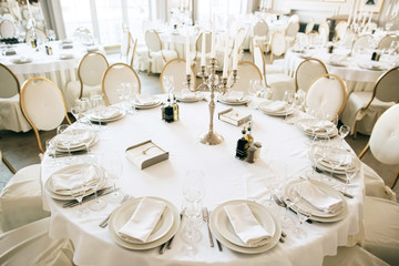 Elegant table arrangement and catering at wedding reception. White style