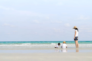 mother and sons playing on beach