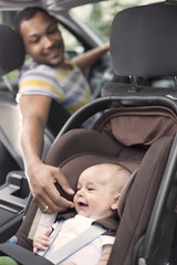 Father cheering baby up while in the car