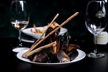 Mussels on a white plate with a glass of wine in a restaurant, side view.