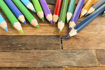 Colored pencils on wooden background. Stock image macro.