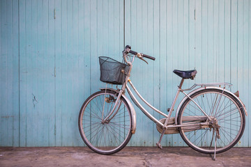 Old classic bicycle with blue wooden door
