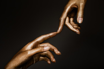 beautiful man's hands in golden paint on black background close up