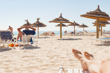 Beach wooden straw sunshade umbrella legs people sunbathing relax Tunisia
