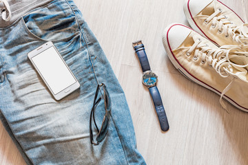 Sport shoe (sneaker) and jeans, Wrist Watch, Sunglasses, smartphone mobile with blank isolated screen for design. Flat lay Male set on wooden background.
