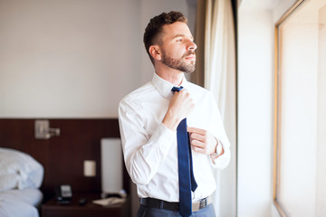 Businessman fixing his tie in a hotel room