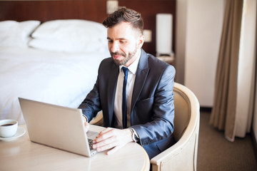 Handsome businessman working on a laptop