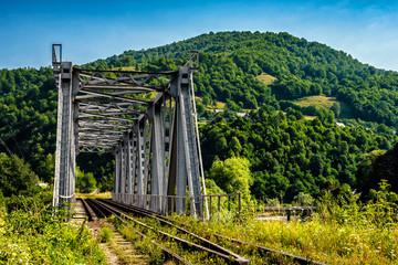 old metal rail road bridge in rural area of Carpathian mountains