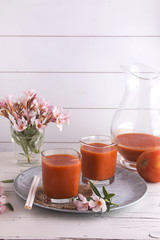 Tomato gazpacho soup in glasses over white background