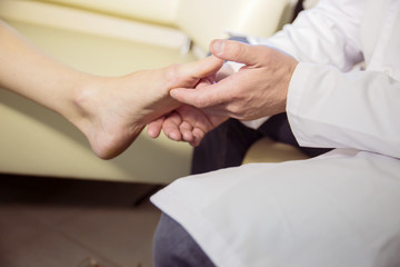 the hands of the doctor examines the foot of a patient
