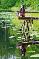 Girl meditation on wooden bridge with water reflection