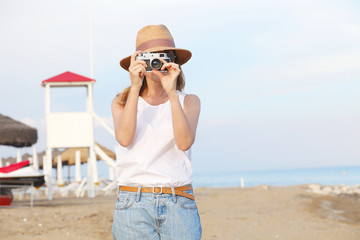 Enjoying summer vacation at the seaside. Woman with photo camera on the beach.