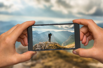 Taking photo of man and mountains with mobile phone
