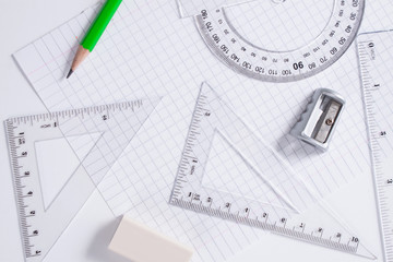 Protractor, rulers, pencil and eraser on squared paper
