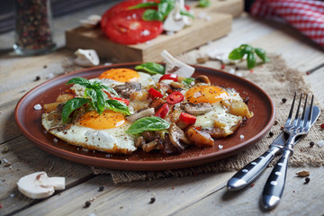 Fried eggs with mushrooms, tomatoes and basil on rustic wooden t