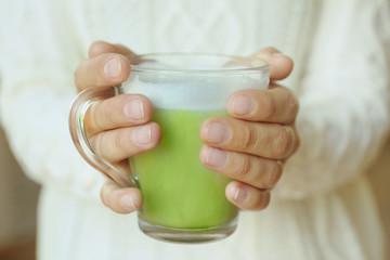 Female hands holding cup of green matcha tea closeup