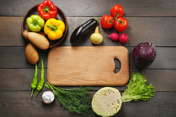 Fresh vegetables and cutting board on wooden background