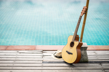 Acoustic guitar leaning on swiming pool.