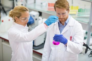 Chemist taking sample from beaker