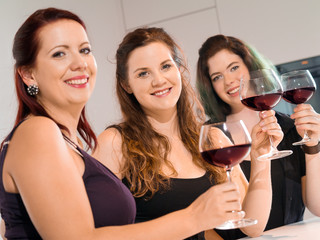 Three women making a toast with wine