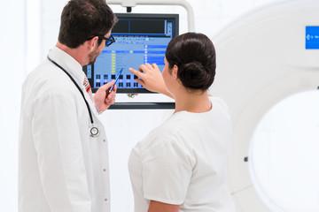 Doktor und Krankenschwester analysieren Daten aus dem CT am Bildschirm im Hospital