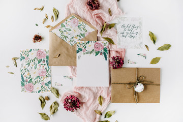 Workspace. Wedding invitation cards, craft envelopes, pink and red roses and green leaves on white background. Overhead view. Flat lay, top view