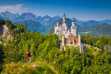 Printed kitchen splashbacks Historical buildings Neuschwanstein Castle with male tourist enjoying the view from a steep cliff, Füssen, Bavaria, Germany