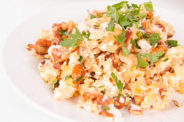 Scrambled eggs with chanterelle and parsley with some white bread on a white background