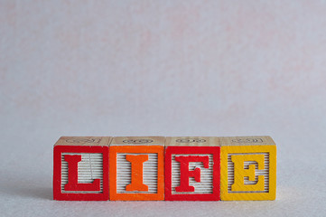 The word life spelled with colorful blocks
