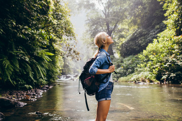 Relaxed female hiker standing by the stream