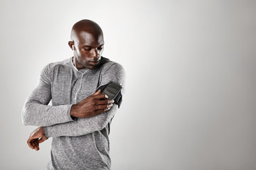 African muscular man listening to music on mobile phone