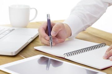 Businessman write a short note on opened notebook with pen and glasses. Flat layout and copy space.