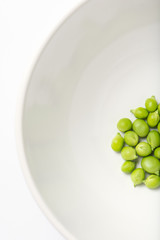 close up of fresh green peas in a white ceramic bowl, overhead view, vertical
