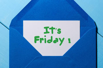 The words It's Friday written on a peace of paper in blue envelope. Happy week concept
