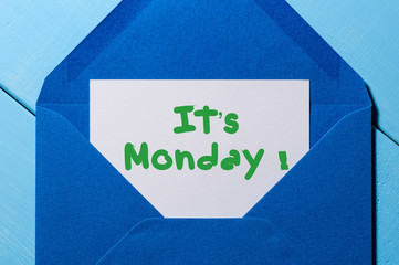 It's Monday on sheet of paper in blue envelope. Happy week concept