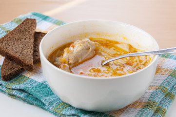 Chicken soup with pasta and brown bread on a towel