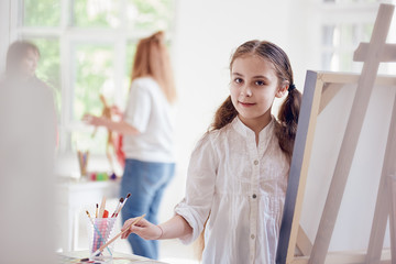 young artist girl about easel